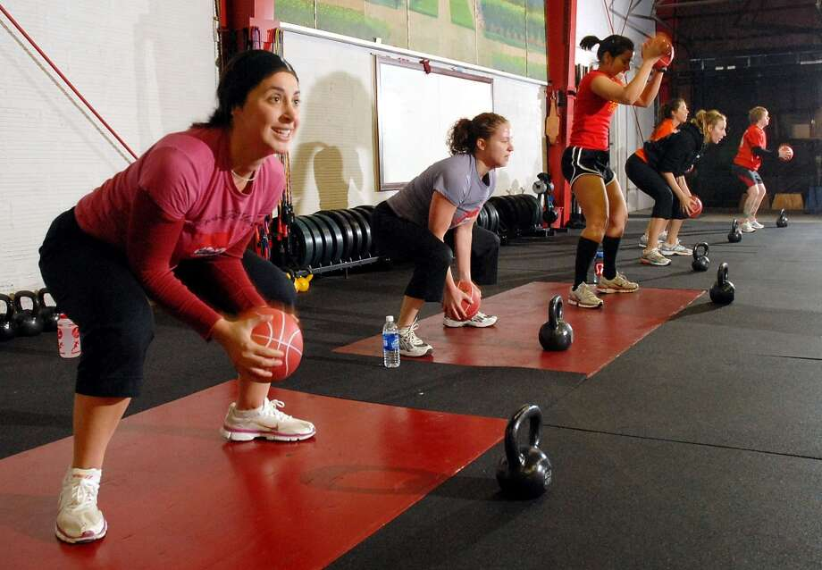 Lauren Hill,at left, and other early risers work out at the 6 a.m. class at Crossfit at their facility on Telephone Rd. Thursday Dec. 04, 2008. (Dave Rossman for the Chronicle) Photo: Dave Rossman, For The Chronicle