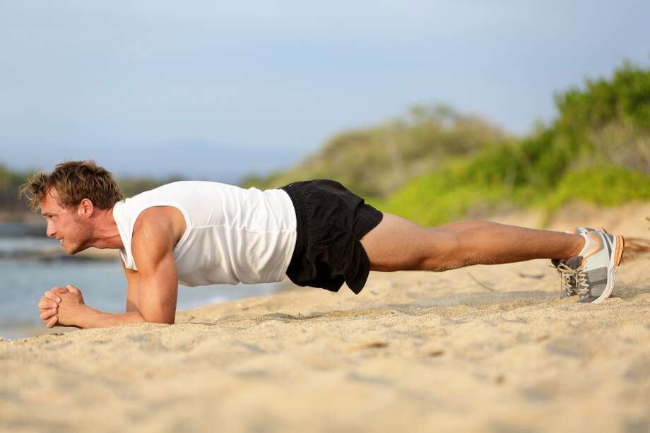 Doing plank exercises can strengthen your core and  help your posture.Crossfit training fitness man doing plank core exercise working out his midsection core muscles. Fit male fitness instructor planking exercising outside in summer on beach. NOT FOR USE BY OTHER HEARST PAPERS. Photo: --, Fotolia