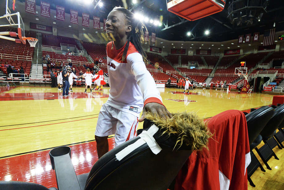 Lamar Lady Cardinals Gia Ayers, No. 1, pays tribute to Lamar University's super fan Morris Keene prior to the start of Thursday's game against Nicholls Colonels at the Montagne Center. Keene passed away Nov. 14, 2013 and since then his legacy as a super fan has continued through his hat which sits on his season ticket holding seat. Michael Rivera/@michaelrivera88   Photo taken Thursday, 01/09/14