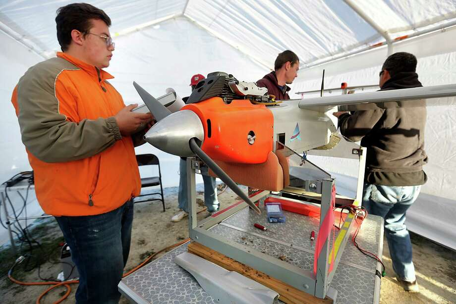 Martin Hass, left, performs a pre-flight check on a RS-16 unmanned aerial vehicle, with Ian Gates, center, and Jack Edward Esparza, right,Texas A&M University-Corpus Christi conducted several test flights of their Unmanned Aircraft System, over South Texas ranch land just outside Sarita, TX on Thursday, Jan. 16, 2014. The RS-16 unmanned aerial vehicle (UAV) was launched and flew for about one and a half hour before it was belly-landed on soft flat sand. Photo: Bob Owen, San Antonio Express-News / ©2013 San Antonio Express-News