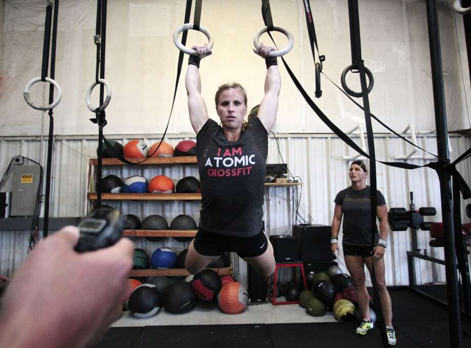 (l-r) Beth Spearman completes a muscle-up on the rings at Atomic CrossFit  as teammate Janet Black supports her in Stafford,Texas, Wednesday, July 17, 2013. Spearman and Black are part of a team of six members training for the Crossfit Games in Carson California that begin July 24. The team is comprised of 3 men and 3 women Beth Spearman, Janet Black, Jamie Carter, Daniel Ward ,Will Maloy, and Benjamin Bacon. ( Billy Smith II / Chronicle ) Photo: Billy Smith II, Chronicle