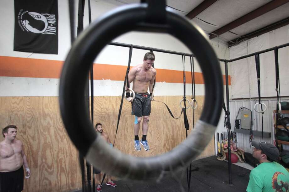 Benjamin Bacon completes a muscle-up on the rings  at Atomic CrossFit in Stafford,Texas, Wednesday, July 17, 2013. Bacon is part of a team of six members training forthe Crossfit Games in Carson California that begin July 24. The team is comprised of 3 men and 3 women Beth Spearman, Janet Black, Jamie Carter, Daniel Ward ,Will Maloy, and Benjamin Bacon. ( Billy Smith II / Chronicle ) Photo: Billy Smith II, Chronicle