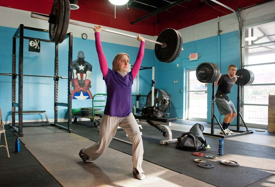 In this photo made Monday, July 11, 2011, Kulsoom Abdullah, left, trains at Crossfit gym in Atlanta, Ga. Abdullah's Ph.D. from Georgia Tech and black belt in taekwondo are proof she doesn't back away from challenges.  Abdullah on Friday will become the first woman to compete in the national weightlifting championships while wearing clothing that covers her legs, arms and head, in keeping with her Muslim faith.  (AP Photo/Joey Ivansco) Photo: Joey Ivansco, Associated Press