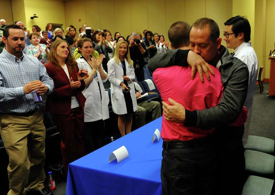 Yale New Haven Hospital personel give a standing ovation to Ryan DaSilva who gets a hug from his father Rolando DaSilva Sr. in New Haven, Conn. on Thursday January 16, 2014. Ryan received his third kidney in a transplant with his brother Rolando Jr. who is standing at left. Photo: Christian Abraham / Connecticut Post