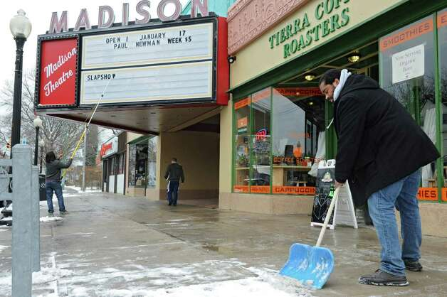 "Madison Theatre employee Antwuan Sims of Albany, shovels the sidewalk as Joseph Alindato of Albany, also an employee at the theatre, places information on the marquee on Thursday, Jan. 16, 2014 in Albany, N.Y. Friday is the grand re-opening of the theatre and will start with classic Paul Newman flicks such as ""Slapshot,"" ""Butch Cassidy and the Sundance Kid,"" Cool Hand Luke"" and ""The Sting."" (Lori Van Buren / Times Union) Photo: Lori Van Buren / 00025401A"