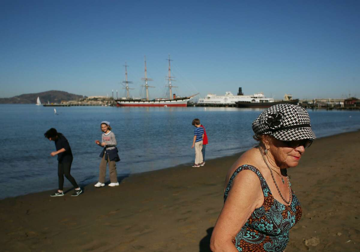 With record warm weather temperatures reaching the bay area, Tatiana Losev, 78, of Concord, walks on the beach after taking a dip in the bay near Aquatic Park on Thursday Jan. 16, 2014 in San Francisco, Calif.