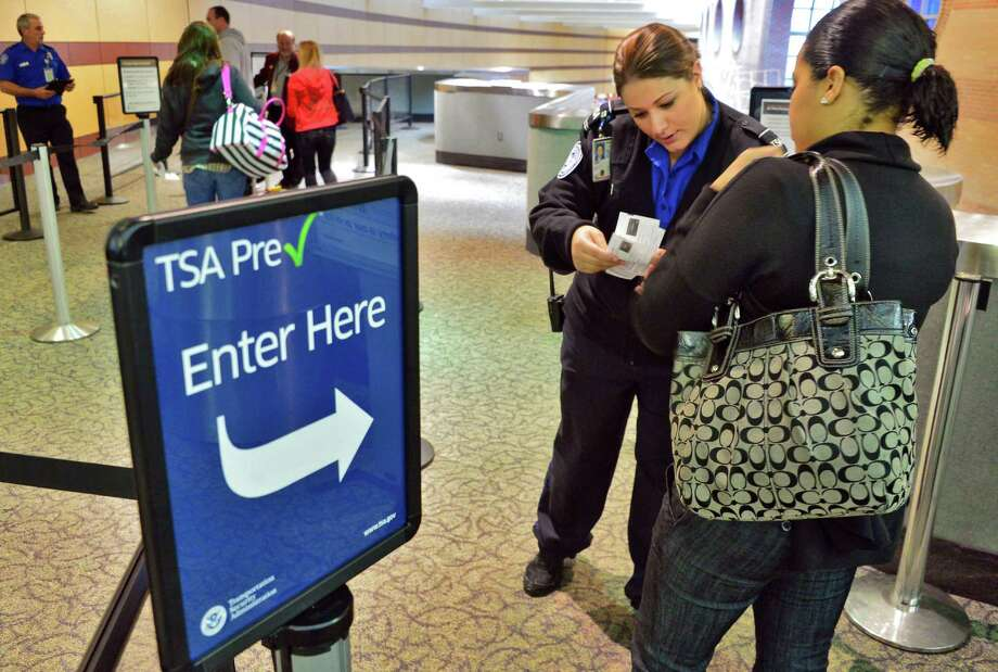 TSA lead officer Maria Deet, center, helps an airline passenger through the TSA's new precheck line at Albany International Airport Thursday Oct. 31, 2013, in Colonie, NY.  (John Carl D'Annibale / Times Union) Photo: John Carl D'Annibale / 00024463A