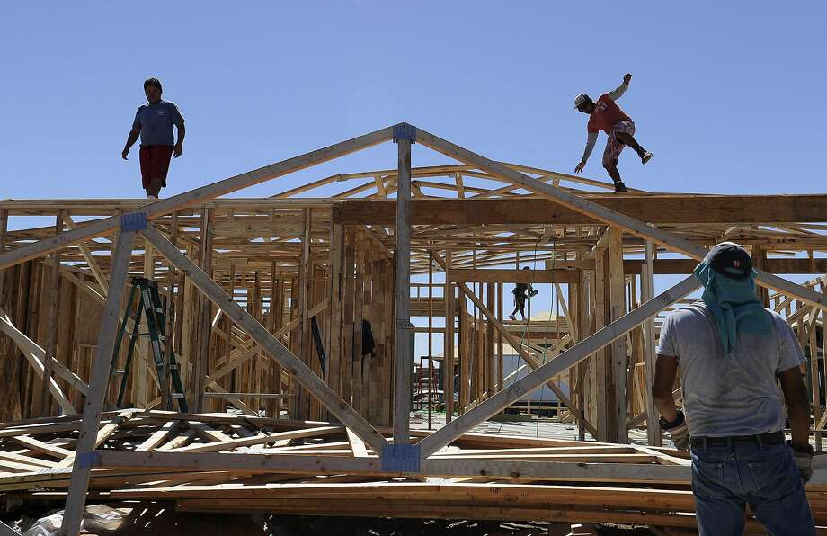 In this Tuesday, Sept. 24, 2013 photo, a man steadies himself as he and others work on framing new houses, in Odessa, Texas. Hundreds of houses are being built in the West Texas oil town to accommodate the influx of people working in the oil fields. (AP Photo/Pat Sullivan) Photo: Pat Sullivan, Associated Press