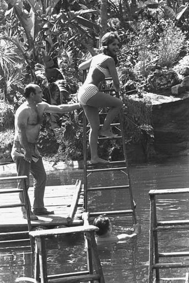 American actress Dawn Wells, in character as Mary Ann, wears a bikini swimsuit as she climbs a ladder above an artifical lagoon with the assistance of two unidentified members of the crew, one of whom is in the water and one of whom is smoking a cigarette, during an episode of the CBS sitcom 'Gilligan's Island' in Studio City, California on April 15, 1966. Photo: CBS Photo Archive, Getty Images / 2007 CBS WORLDWIDE INC.
