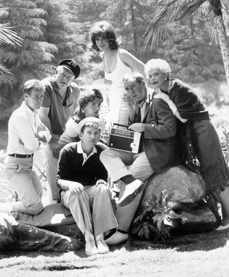 The cast of the television comedy series, 'Gilligan's Island,' which ran from 1964-1967, listens to a short wave radio outdoors in a promotional portrait. Pictured from left to right are Actors Russell Johnson, Alan Hale Jr., Dawn Wells, Bob Denver, Tina Louise, Jim Backus, and Natalie Schafer. Photo: Hulton Archive, Getty Images / Archive Photos