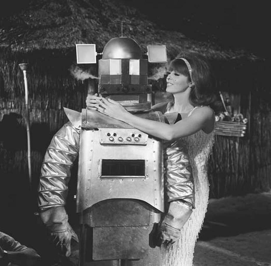 American actress Tina Louise, as Ginger, wraps her arms around the 'shoulders' of a robot (played by Bob D'Arcy) in a scene from an episode of the television comedy 'Gilligan's Island' entitled 'Gilligan's Living Doll' in Los Angeles, California on November 18, 1965. The episode was originally broadcast on February 10, 1966. Photo: CBS Photo Archive, Getty Images / 2008 CBS WORLDWIDE INC.