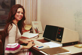 A woman in a knit dress with flared sleeves works at an early model desktop computer made by Servus, 1970s.