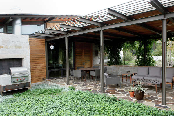 A home in Leon Springs has a main house and a guest house with a covered patio connecting the two. The house is also eco friendly with solar panels covering the car port and water tanks near the pool.