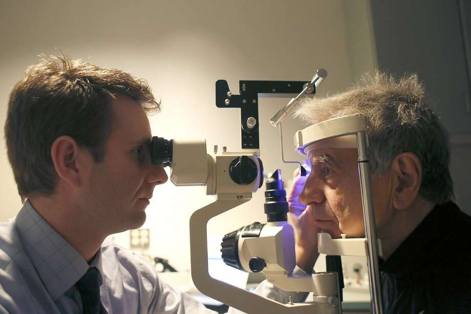 Dr. Isaac Porter (left) examines Neville Wood's eyes at his clinic in Raleigh, N.C., in January. Porter uses Google+ to communicate with patients. Photo: Travis Long, McClatchy-Tribune News Service
