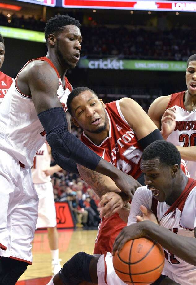 Houston's TaShawn Thomas, center, battles Louisville's Mangok Mathiang, right, and Montrezl Harrell for a loose ball during the first half of an NCAA college basketball game, Thursday, Jan. 16, 2014, in Louisville, Ky. (AP Photo/Timothy D. Easley) Photo: Associated Press