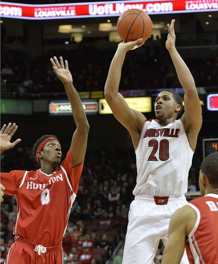 Louisville's Wayne Blackshear, right, puts up a shot over the defense of Houston's Danrad Knowles during the second half of an NCAA college basketball game, Thursday, Jan. 16, 2014, in Louisville, Ky. Louisville defeated Houston 91-52, and Blackshear led all scorers with 23 points. (AP Photo/Timothy D. Easley) Photo: Associated Press