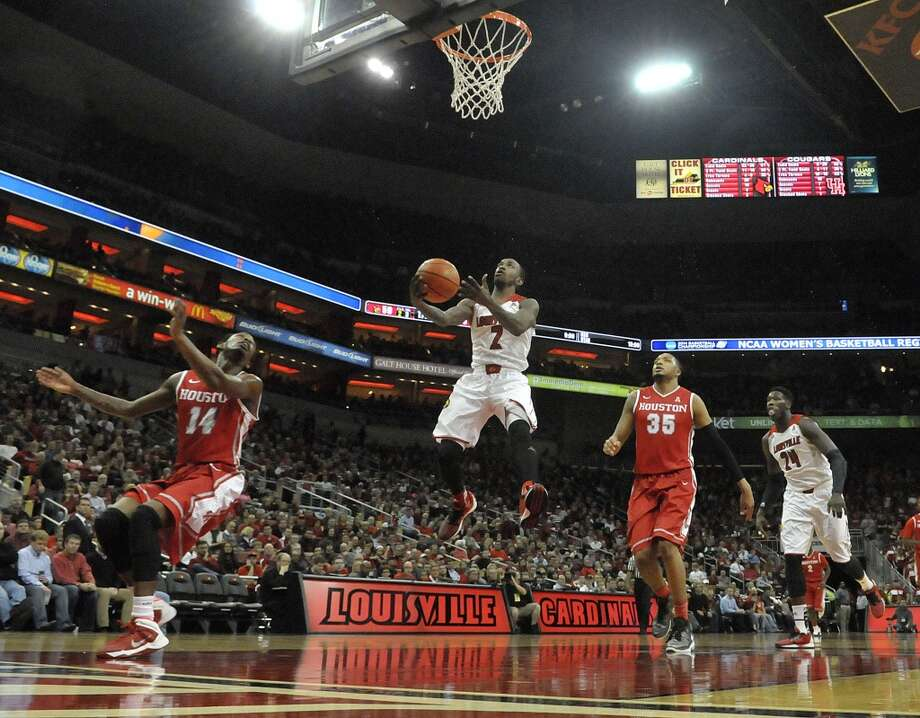 Louisville's Russ Smith, center, goes in for a layup between the defense of Houston's Tione Womack, left, and Tashawn Thomas during the second half of an NCAA college basketball game Thursday, Jan. 16, 2014, in Louisville, Ky. Louisville defeated Houston 91-52. (AP Photo/Timothy D. Easley) Photo: Associated Press