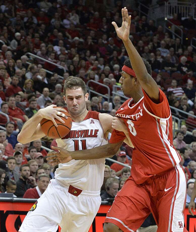 Houston's Danrad Knowles, right, attempts to take the ball away from Louisville's Luke Hancock during the second half of an NCAA college basketball game, Thursday, Jan. 16, 2014, in Louisville, Ky. Louisville defeated Houston 91-52. (AP Photo/Timothy D. Easley) Photo: Associated Press