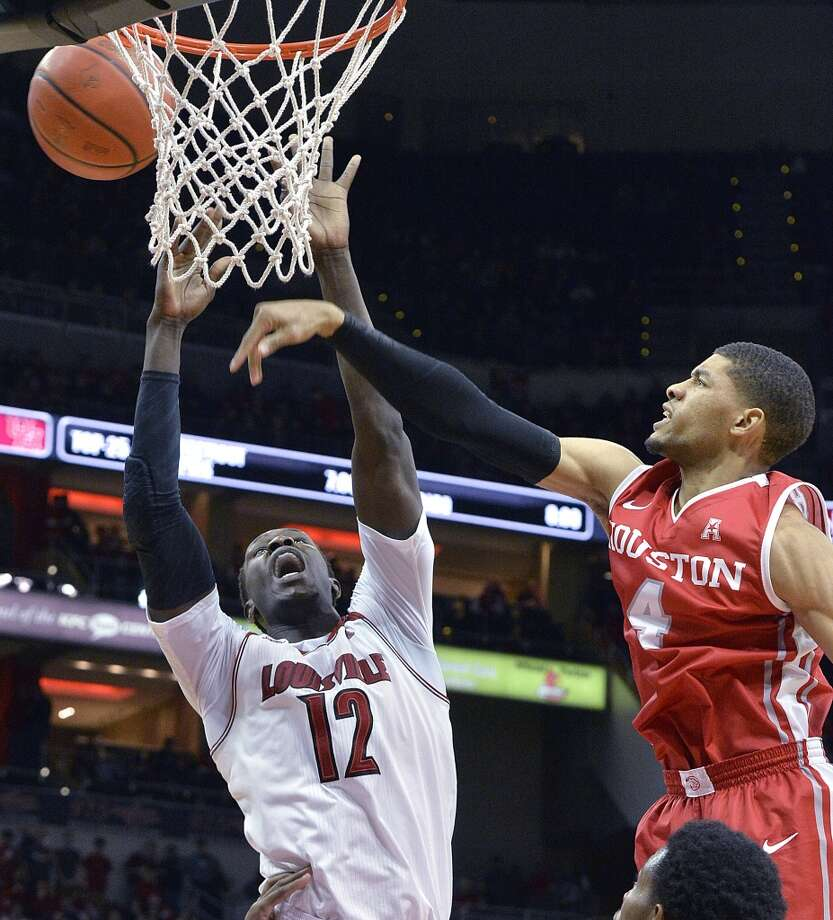 Louisville's Mangok Mathiang, left, attempts to grab a rebound away from Houston's LeRon Barnes during the second half of an NCAA college basketball game Thursday, Jan. 16, 2014, in Louisville, Ky. Louisville defeated Houston 91-52. (AP Photo/Timothy D. Easley) Photo: Associated Press