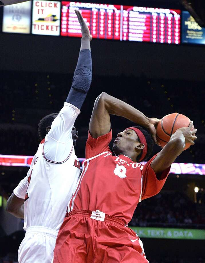 Houston's Danrad Knowles, right, gets a shot off over the defense of Louisville's Mangok Mathiang during the first half of an NCAA college basketball game, Thursday, Jan. 16, 2014, in Louisville, Ky. (AP Photo/Timothy D. Easley) Photo: Associated Press