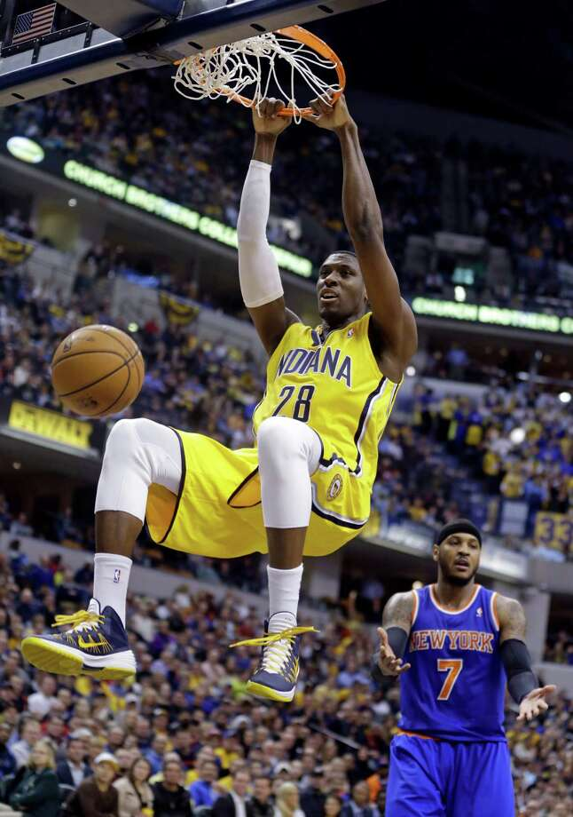 Indiana Pacers center Ian Mahinmi (28) gets a dunk in front of New York Knicks forward Carmelo Anthony during the second half of an NBA basketball game in Indianapolis, Thursday, Jan. 16, 2014. The Pacers defeated the Knicks 117-89. (AP Photo/Michael Conroy) ORG XMIT: NAF113 Photo: Michael Conroy / AP