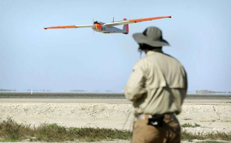 Michael Cancienne guides the RS-16 unnmanned aerial vehicle toward a landing on a South Texas ranch after a flight Thursday. Photo: Bob Owen, Staff / ©2013 San Antonio Express-News