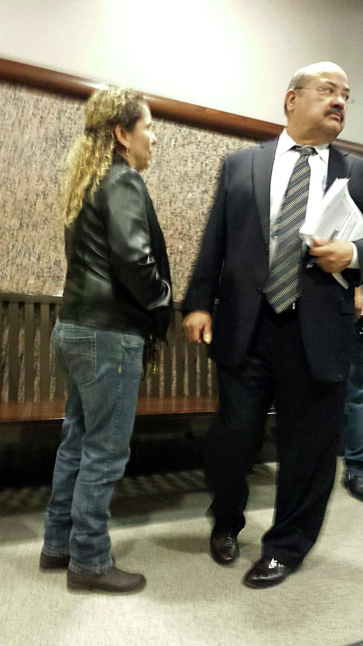 Al Acevedo Jr., right, confers with a client as he sheds his cases on Tuesday, Jan. 14, 2014. Acevedo has withdrawn from his state and federal cases as he negotiates with federal authorities investigating him and corruption at the Bexar County Courthouse.
