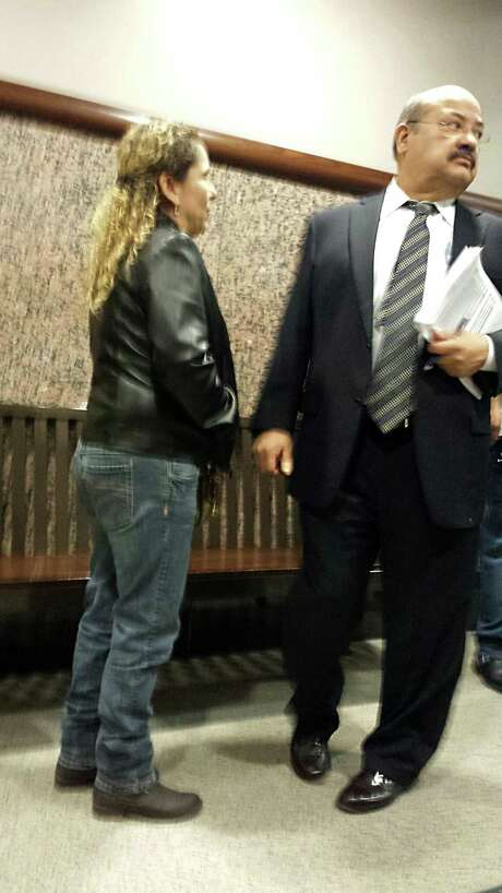 Al Acevedo Jr., right, confers with a client as he sheds his cases on Tuesday, Jan. 14, 2014. Acevedo has withdrawn from his state and federal cases as he negotiates with federal authorities investigating him and corruption at the Bexar County Courthouse. Photo: Guillermo Conteras, San Antonio Express-News / San Antonio Express-News