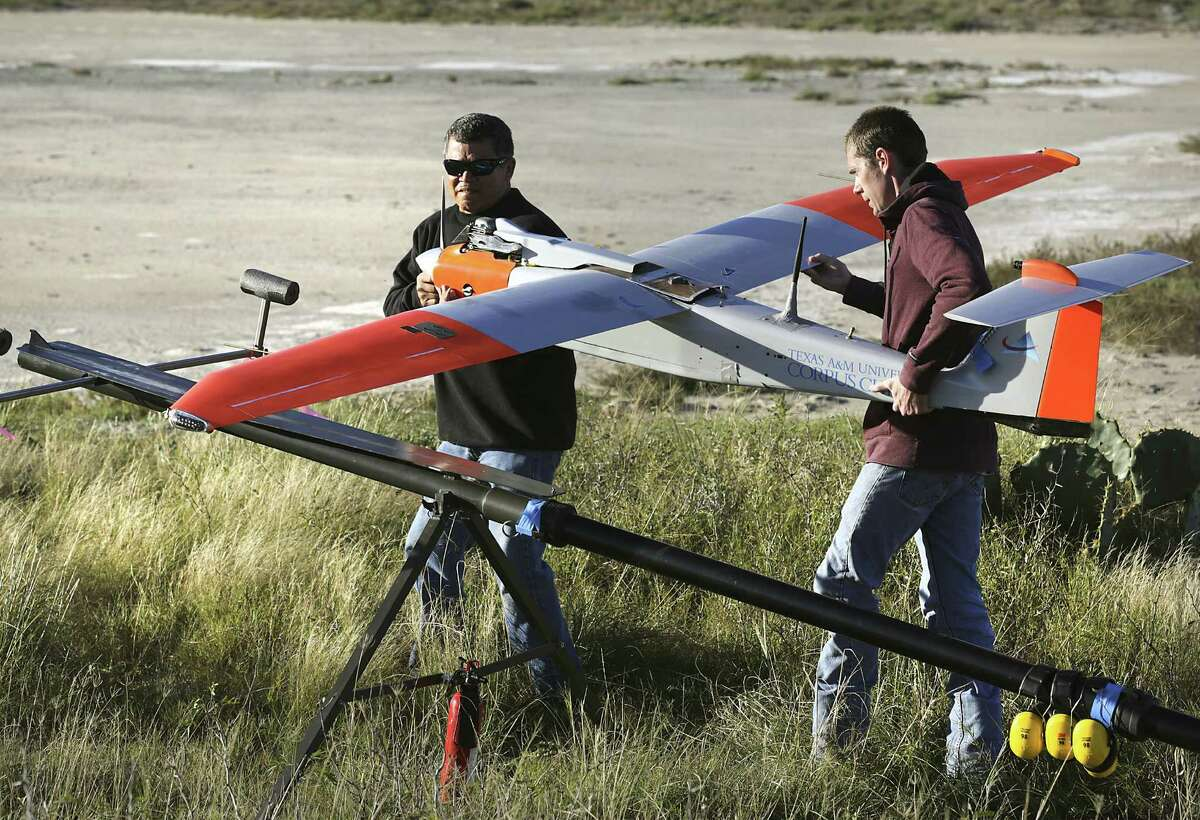 Jack Edward Esparza (left) and Ian Gates load the RS-16 on its launching pad. Texas A&M University-Corpus Christi conducted several test flights of the drone over ranchland.