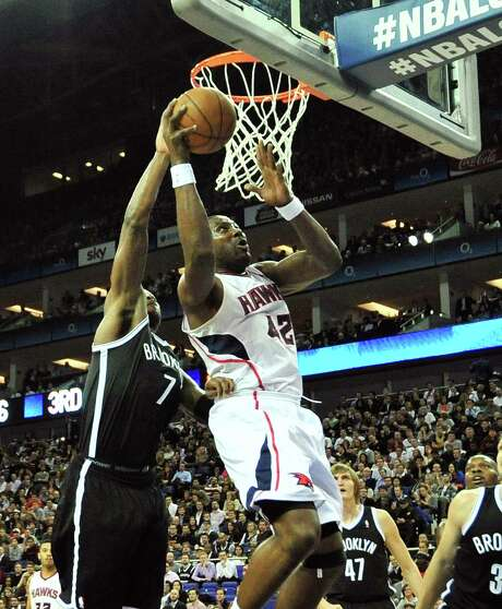 Brooklyn guard Joe Johnson (left), who scored 26 of his 29 points in the first half, tries to block Atlanta forward Elton Brand at the O2 Arena in London. Photo: Glyn Kirk / Getty Images / AFP