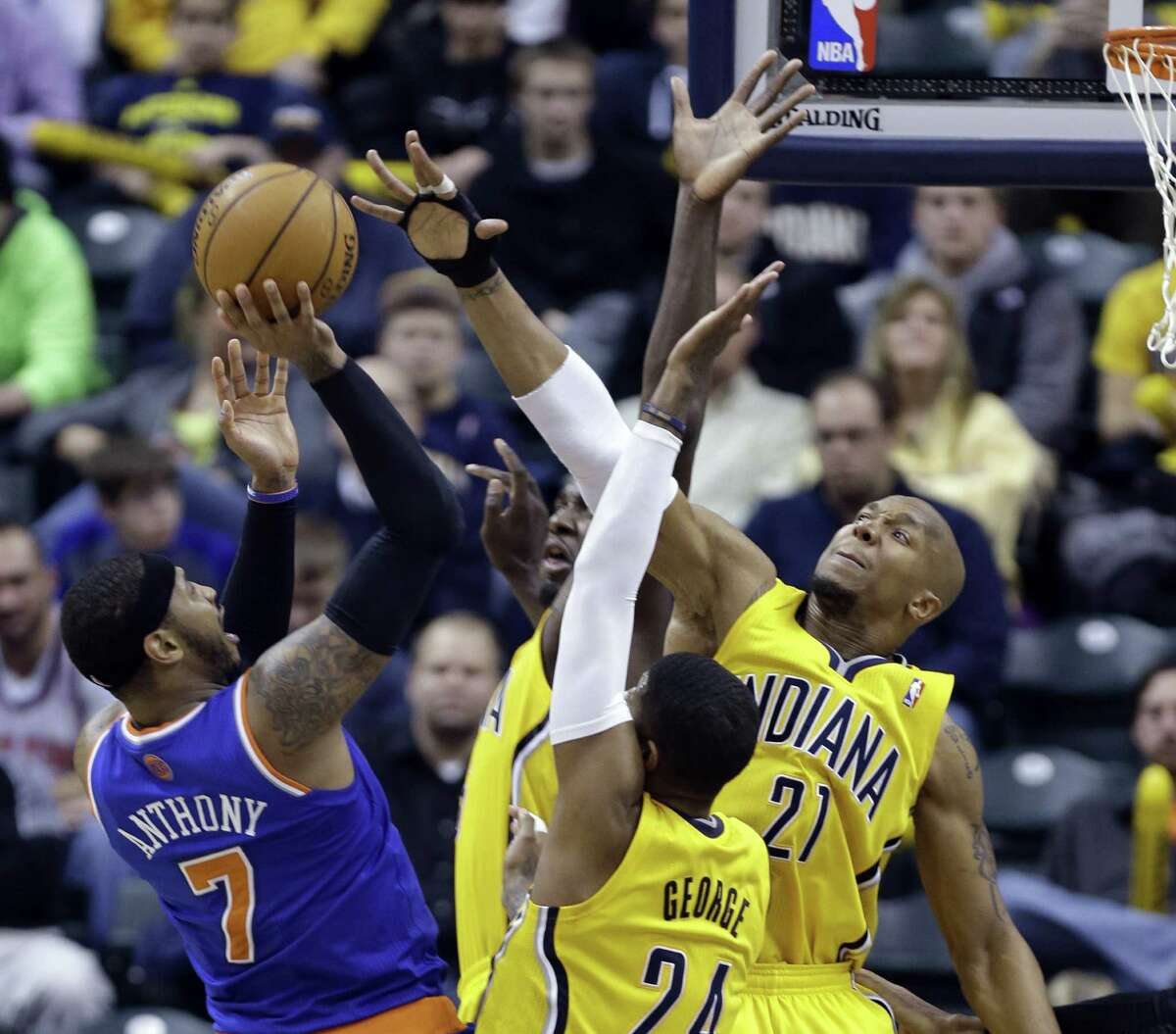Knicks forward Carmelo Anthony tries to shoot over the Pacers' Paul George (24), David West (21) and Roy Hibbert (partially hidden, center) during Indiana's blowout victory at Bankers Life Fieldhouse.