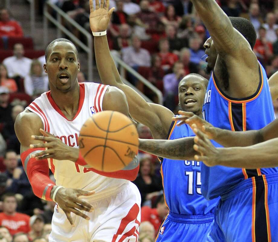 Rockets power forward Dwight Howard (12) passes the ball under the basket. Photo: Karen Warren, Houston Chronicle