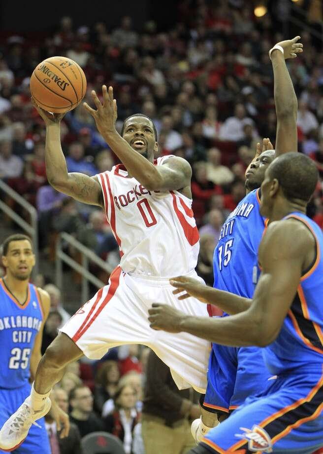 Rockets point guard Aaron Brooks (0) goes up for a basket against Thunder point guard Reggie Jackson. Photo: Karen Warren, Houston Chronicle