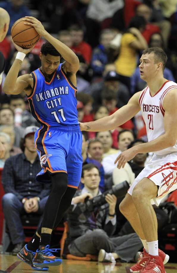 Thunder shooting guard Jeremy Lamb (11) checks his feet as Rockets power forward Donatas Motiejunas defends. Photo: Karen Warren, Houston Chronicle