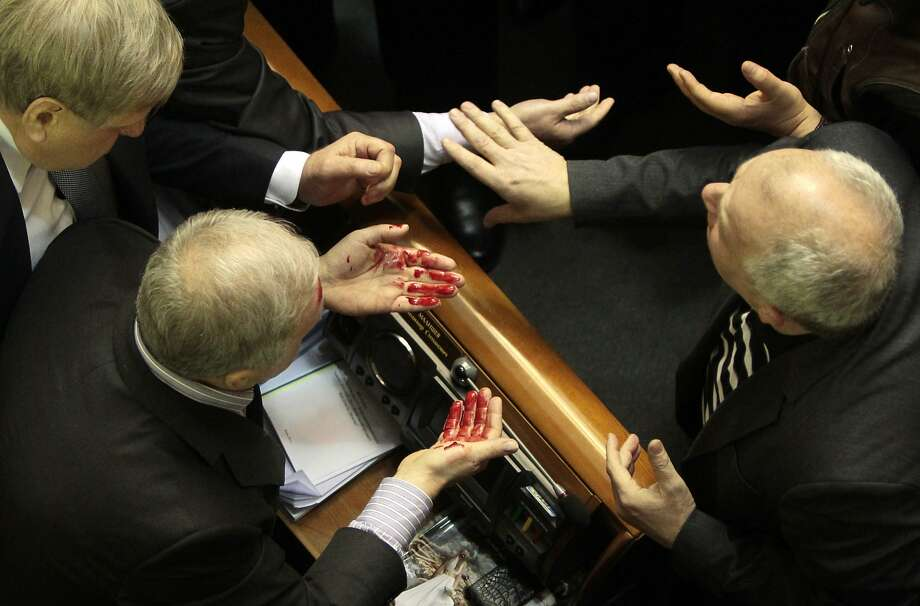 Ukrainian pro-government lawmaker Volodymyr  Malyshev, left, wipes blood from his face after a scuffle in the Ukrainian parliament  in Kiev, Ukraine, Thursday, Jan. 16, 2014. Lawmakers scuffled in the Ukrainian parliament during a debate on this year's budget. Despite the opposition's efforts to disrupt the vote,  the budget draft, which has already been delayed by almost two months, was passed in its second reading. (AP Photo/Sergei Chuzavkov) Photo: Sergei Chuzavkov, Associated Press