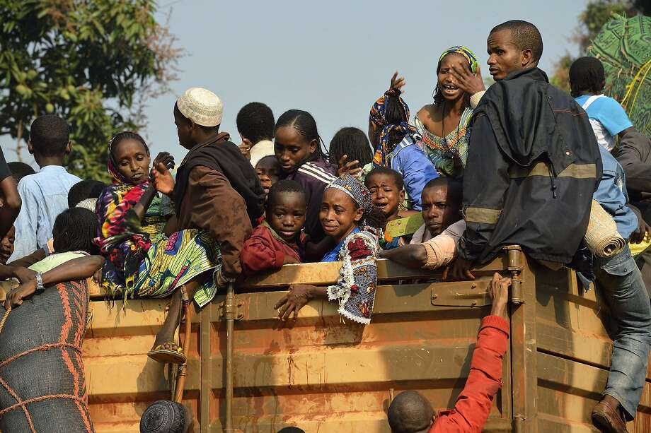 TOPSHOTS Chadian civilians sit on a Chadian military truck in the PK12 district of Bangui on January 16, 2014 to flee the Central African Republic and return to Chad. At least seven people were killed in overnight violence in Bangui, according to a compiled toll from the Red Cross and AFP. Tensions remain high in the city, where French forces are patrolling in a bid to quell unrest that continues to simmer between Muslim ex-rebels and the Christian majority. AFP PHOTO / ERIC FEFERBERGERIC FEFERBERG/AFP/Getty Images Photo: Eric Feferberg, AFP/Getty Images
