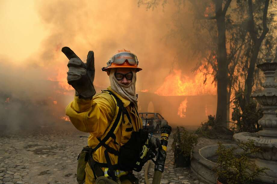 A fireman calls for more water on the burning Singer home above Glendora, Calif., Thursday Jan. 16, 2014.  The wildfire in the foothills of Southern California's San Gabriel Mountains, burned a portion of the former Singer home, of sewing machine fame.  (AP Photo/The Inland Valley Daily Bulletin,Will Lester)  MANDATORY CREDIT Photo: Will Lester, Associated Press