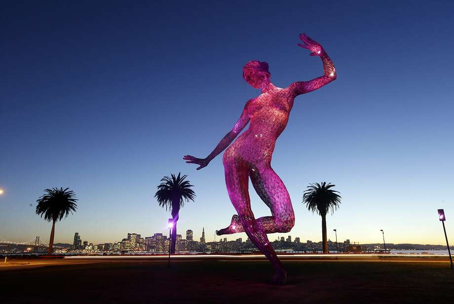 The sculpture Bliss Dance by artist Marco Cochrane towers over the San Francisco skyline at dusk in a view from Treasure Island on Thursday, Jan. 16, 2014, in San Francisco. The 40-foot sculpture of a dancing woman was originally designed for the Burning Man festival in the Nevada desert. It weighs 7000 pounds with an array of 1000 slowly changing l.e.d. colored lights. (AP Photo/Marcio Jose Sanchez) Photo: Marcio Jose Sanchez, Associated Press