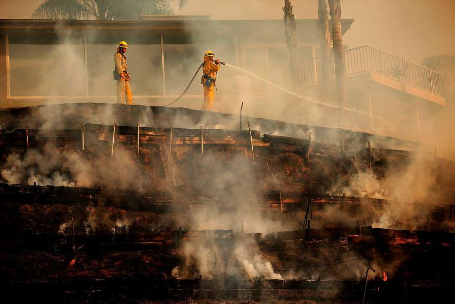Firefighters hose down smoldering embars near a home as the Colby fire burns in Glendora, Calif., on Thursday, Jan. 16, 2014. (Robert Gauthier/Los Angeles Times/MCT) Photo: Robert Gauthier, McClatchy-Tribune News Service