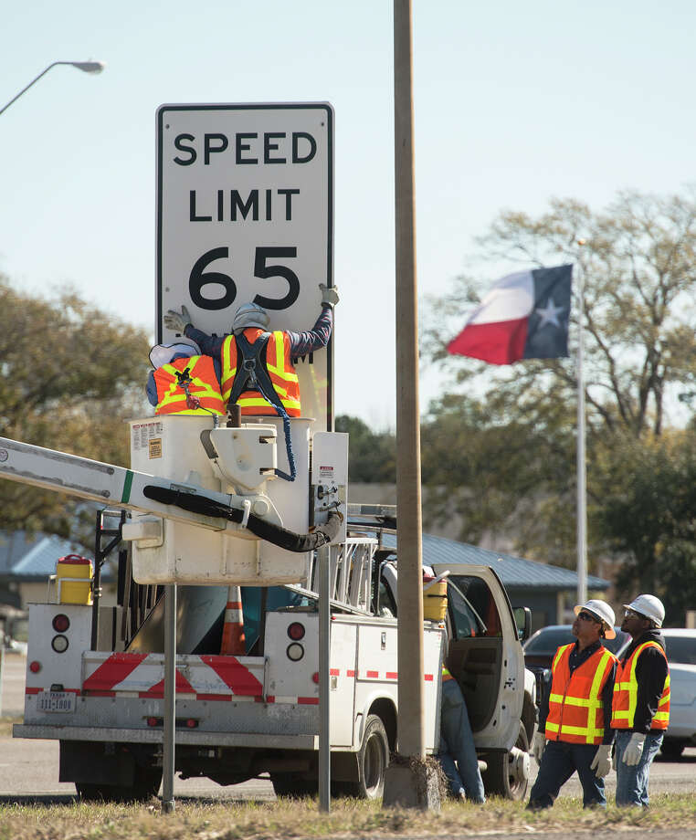 Two workers detach a speed limit sign along Highway 69 while others wait below to help take it down Thursday. While roadwork continued along Eastex Freeway, work crews removed the 65 MPH signs along Highway 69 on Thursday. The speed limit is being reduced to 55 to aide in the ramp reversal project. Photo taken Thursday, 1/16/14 Jake Daniels/@JakeD_in_SETX Photo: Jake Daniels / ©2013 The Beaumont Enterprise/Jake Daniels