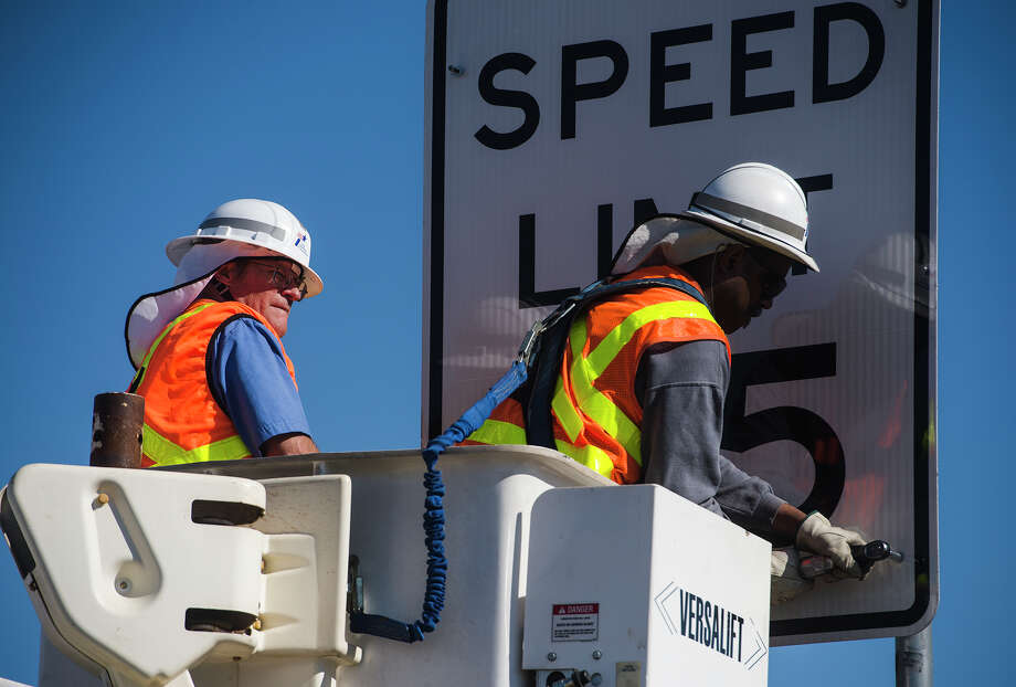 Walter Koenig, left, looks on as Mark Gilder tightens up a final bolt on one a speed limit sign along Highway 69. Jake Daniels/@JakeD_in_SETX Photo: Jake Daniels / ©2013 The Beaumont Enterprise/Jake Daniels