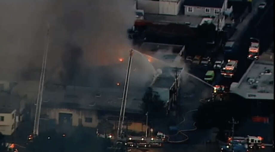 Fire crews battle a smokey fire that surged to six-alarms early Friday morning in Redwood City. Photo: CBS San Francisco