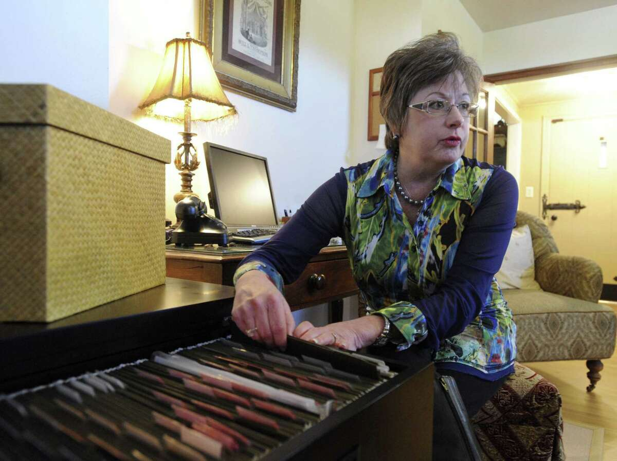 Kat Jacoby, president of Divine Organization, looks through files she helped organize in a client's home in Comfort.