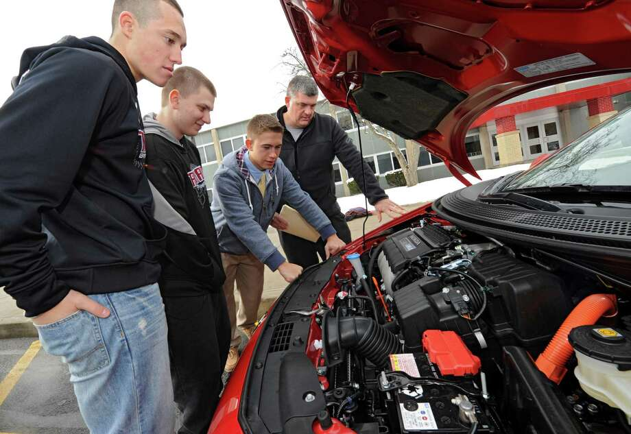 From left, Luke Mancini, 17; Morgan Trembley, 18; Brett Sarnowski, 17; and teacher Rick Warren check out under the hood of a Honda CRZ hybrid car as seniors drive and compare alternative fuel cars at Scotia-Glenville High School on Friday Jan. 17, 2014 in Scotia, N.Y. The students have been studying alternative fuel and energies in their English 12, Career Writing/Media Analysis class with teacher Rick Warren.  (Lori Van Buren / Times Union) Photo: Lori Van Buren / 00025366A