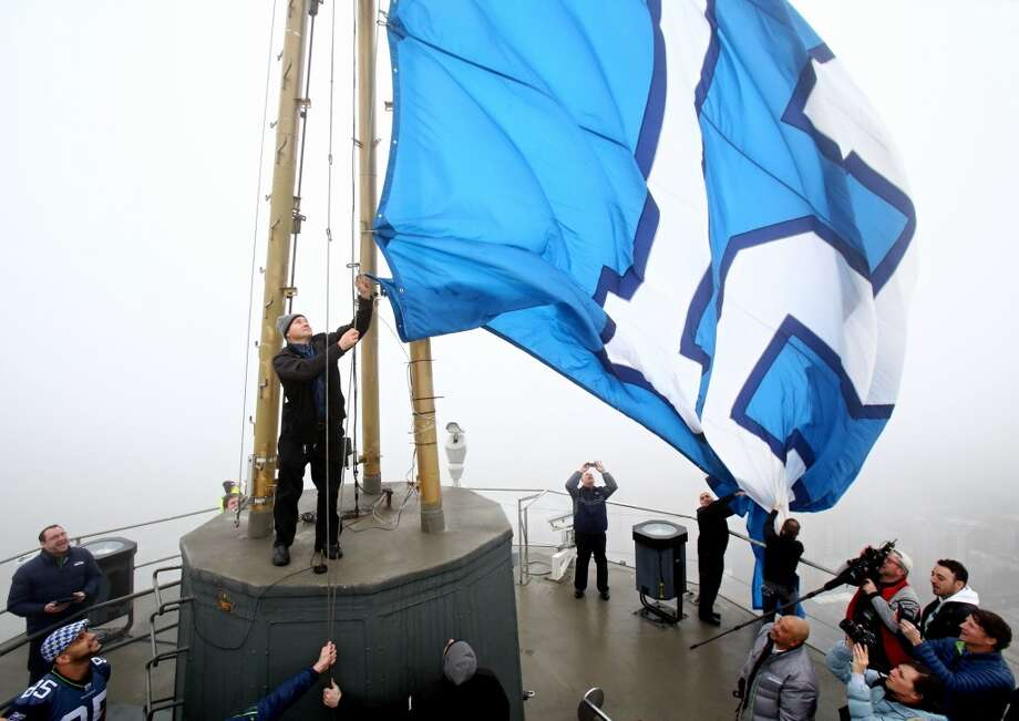Former Seahawks player Joe Tafoya raises the 12th Man flag on top of the Space Needle Friday morning. (Joshua Trujillo/seattlepi.com) Photo: Joshua Trujillo, Seattlepi.com