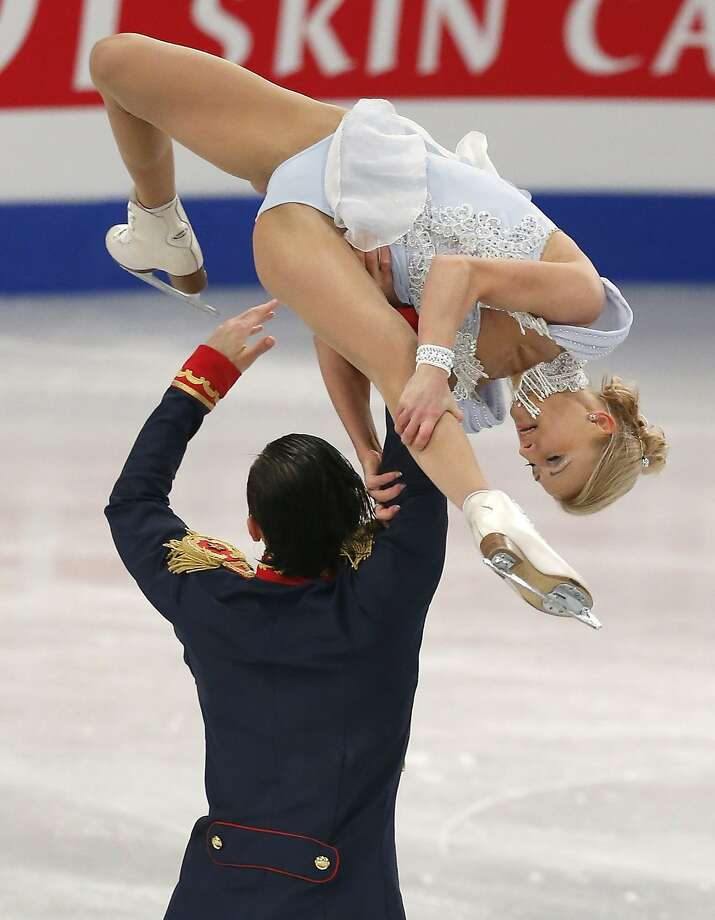 Somehow avoiding dizziness,Russia's Tatiana Volosozhar and Maxim Trankov perform a difficult maneuver in the pairs short program at the European Figure Skating Championships in Budapest. Photo: Darko Bandic, Associated Press