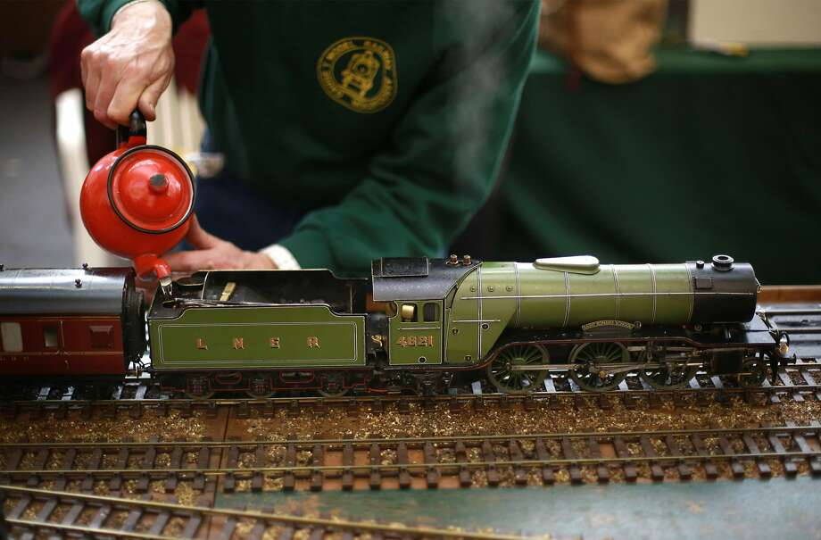 Tea is for train: Model railroad enthusiast Adam Houghton fills the tender of his working steam locomotive at the London Model Engineering Exhibition at Alexandra Palace. Photo: Peter Macdiarmid, Getty Images