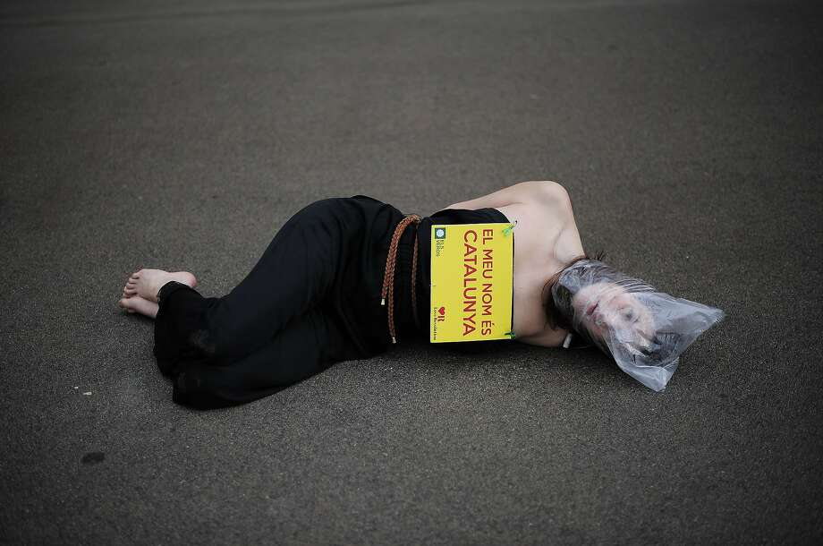"Bagged and bound:A protester wearing a plastic bag on her head and a banner reading ""My name is Catalonia"" lies on the ground outside Catalonia's parliament in Barcelona. Catalonia lawmakers voted to demand the right to hold a referendum on declaring independence from Spain. Photo: Josep Lago, AFP/Getty Images"
