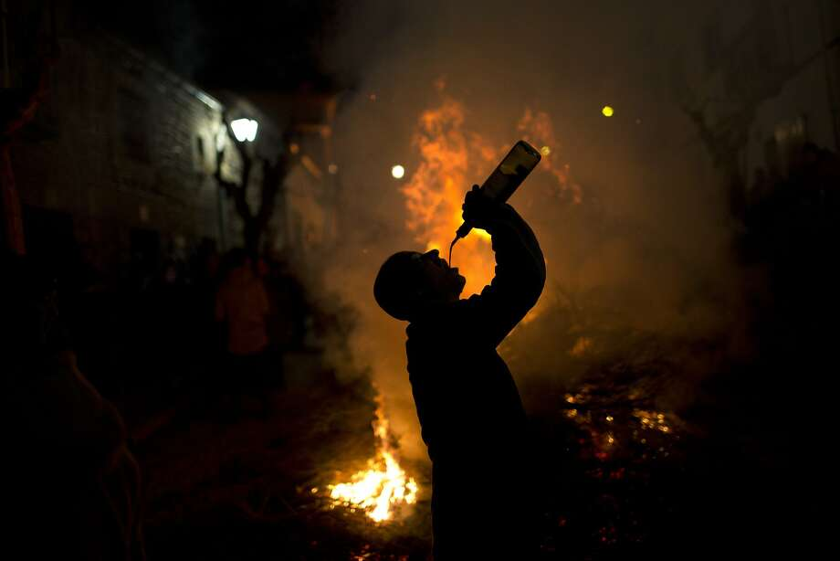 The horses may be trained to walk through bonfires on the eve of Saint Anthony's Day in San Bartolome de Pinares, but some of the revelers require a little liquid courage. Photo: Emilio Morenatti, Associated Press