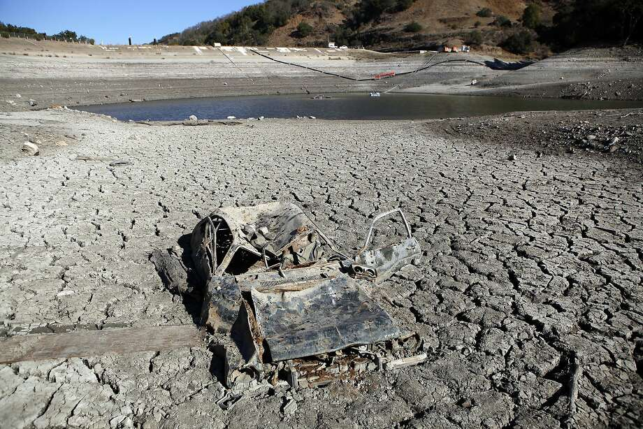 Due to the ongoing drought, receding waters at the Almaden Reservoir have revealed a car that was illegally dumped years ago and is now stuck in the lake bed, in San Jose. Photo: Michael Short, The Chronicle